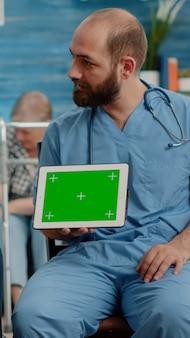 Mężczyzna pielęgniarka i stary pacjent patrzący na zielony ekran na tablecie
