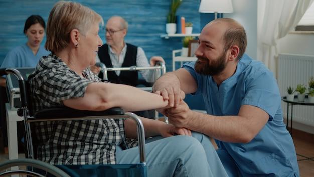 Mężczyzna pielęgniarka pociesza emerytowaną kobietę z niepełnosprawnością