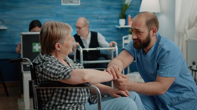 Mężczyzna pielęgniarka pociesza starszą kobietę z przewlekłymi problemami