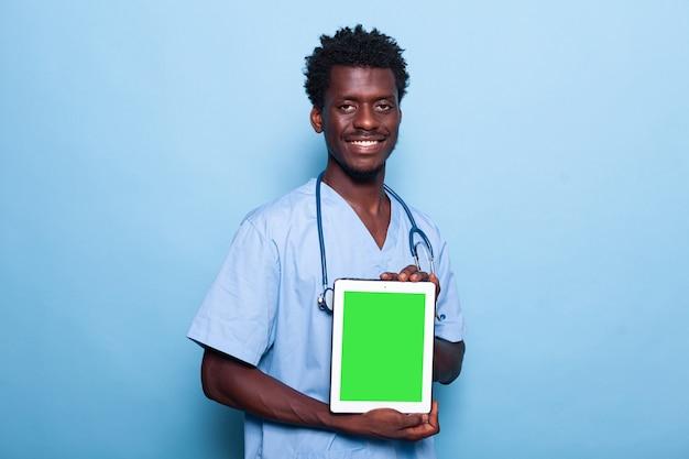 Mężczyzna pielęgniarka pokazuje pionowy zielony ekran na tablecie