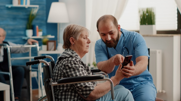 Mężczyzna pielęgniarka uczy emerytowaną kobietę z niepełnosprawnością obsługi smartfona
