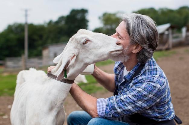 Mężczyzna pieści kozę