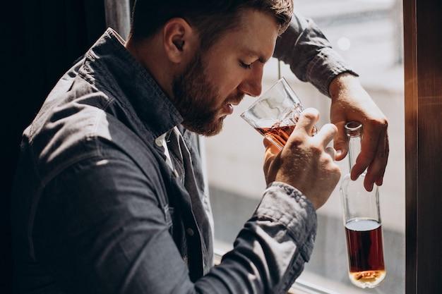 Mężczyzna pijący przygnębiony butelką whisky?