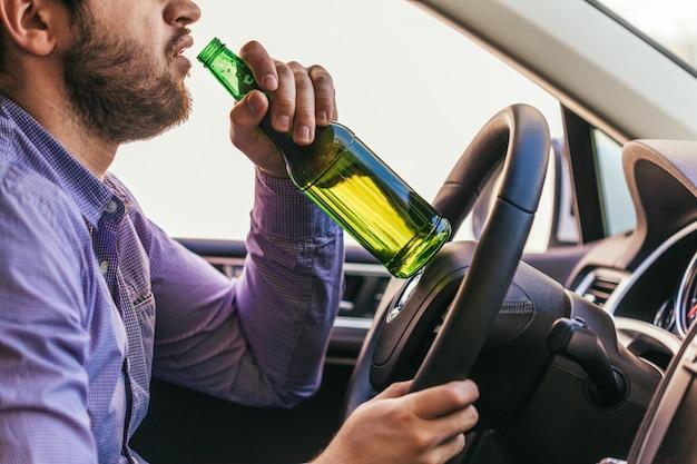 Mężczyzna pije alkohol podczas prowadzenia samochodu