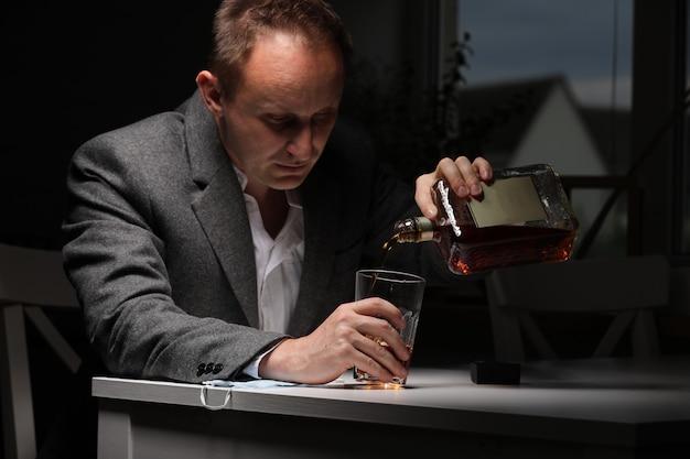 Mężczyzna pije alkohol w kuchni. facet czuje zatrucie i ból dotyka bolącej głowy. uzależnienie od alkoholu