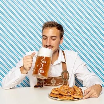 Mężczyzna pije blondynki piwo z wzorzystym tłem