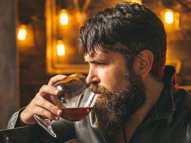 Mężczyzna pije brandy lub whisky. brodaty mężczyzna w kurtce i pije brandy whisky lub koniak