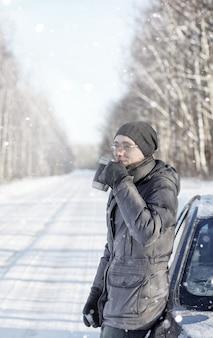 Mężczyzna pije gorącą herbatę z kubka na zewnątrz na zimowej drodze