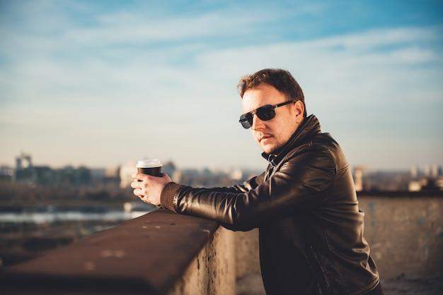 Mężczyzna pije kawę na dachu