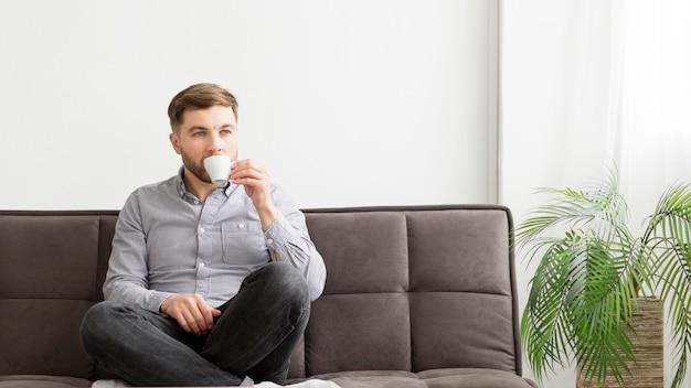 Mężczyzna pije kawę na kanapie