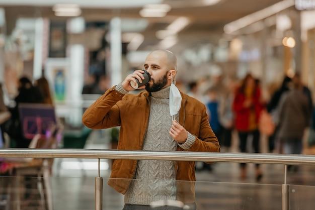 Mężczyzna pije kawę podczas zdejmowania maseczki medycznej w centrum handlowym. łysy facet zachowuje dystans społeczny.