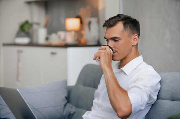 Mężczyzna pije kawę relaksując się na kanapie w domu