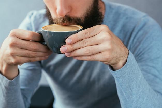 Mężczyzna pije kawę. tradycyjny gorący napój energetyzujący