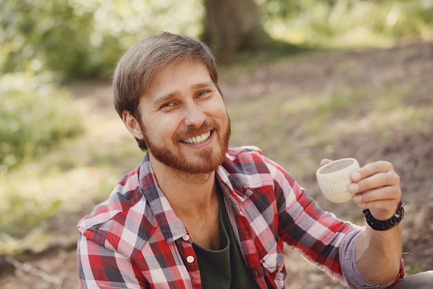Mężczyzna pije kawę w lesie