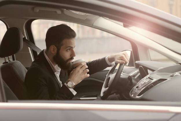 Mężczyzna pije kawę w samochodzie