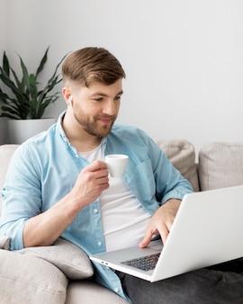 Mężczyzna pije kawę z laptopem