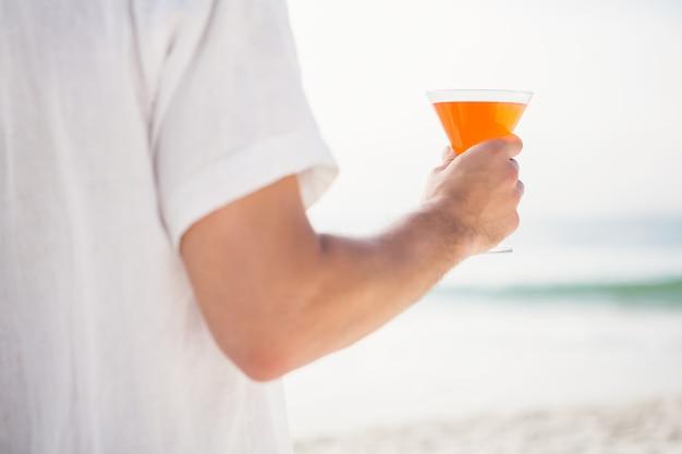 Mężczyzna pije koktajl na plaży