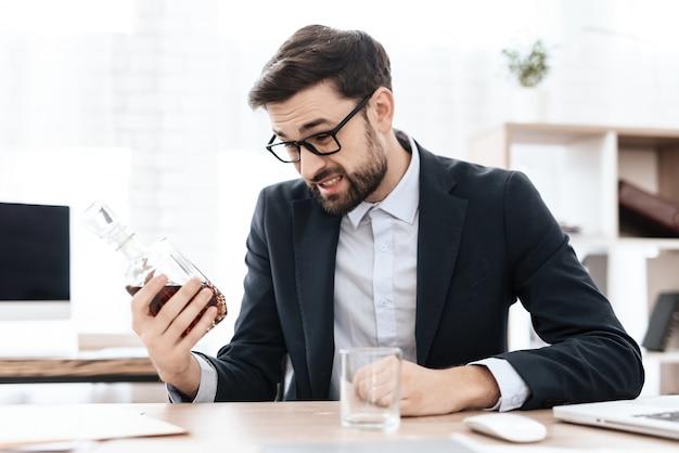 Mężczyzna pije napój alkoholowego w miejscu pracy.
