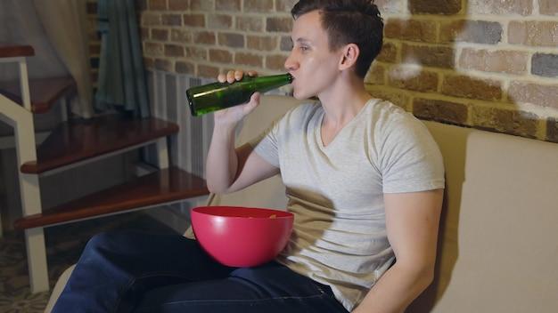 Mężczyzna pije piwo i frytki przed telewizorem.