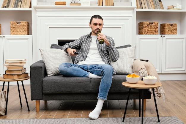 Mężczyzna pije piwo i ogląda telewizję, siedząc na kanapie