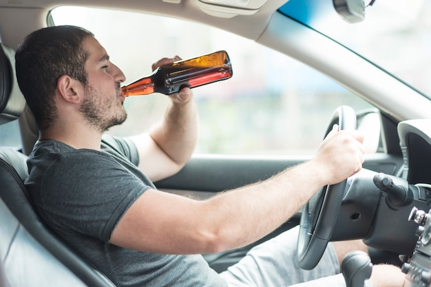 Mężczyzna pije piwo w samochodzie