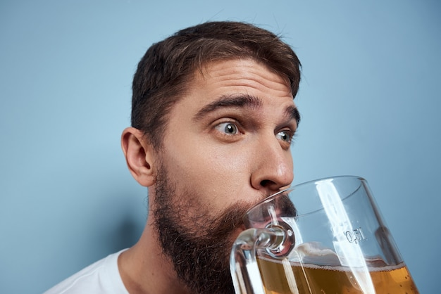 Mężczyzna pije piwo ze szklanki i je fast-food smażone śmieci