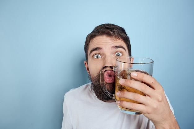 Mężczyzna pije piwo ze szklanki i zjada fastfood smażone śmieci
