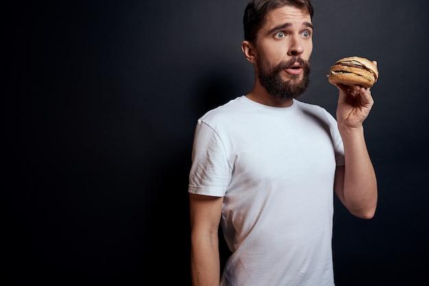 Mężczyzna pije piwo ze szklanki i zjada niezdrowe smażone fast foody