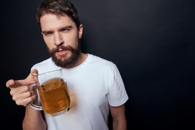 Mężczyzna pije piwo ze szklanki i zjada smażone fast foody