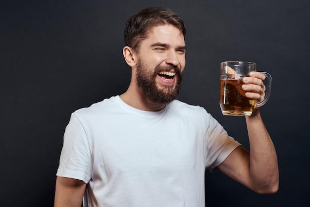Mężczyzna pije piwo ze szklanki i zjada śmieciowe fast foody