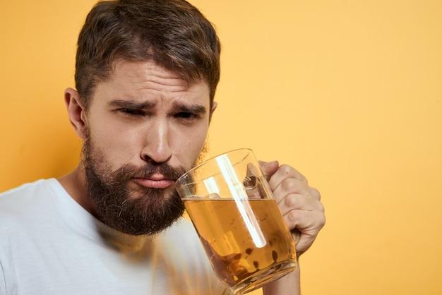 Mężczyzna pije piwo ze szklanki