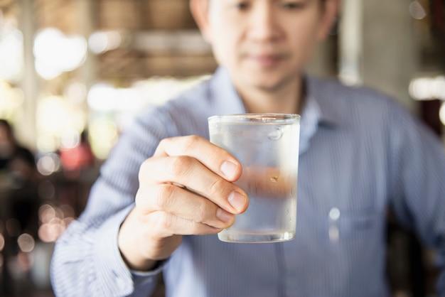 Mężczyzna pije świeżą zimną czystą wodę w szkle