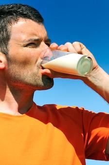 Mężczyzna pije szklankę świeżego mleka w błękitne niebo