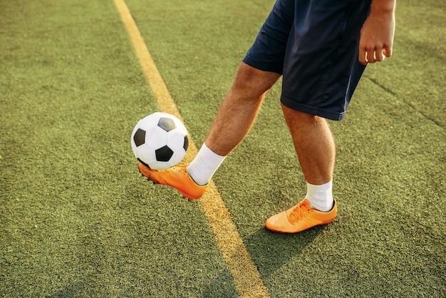 Mężczyzna piłkarz z piłką stojącą na linii na boisku. piłkarz na stadionie, trening przed meczem piłki nożnej