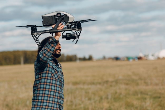 Mężczyzna pilot trzyma drona dji inspire 2 w rękach na zewnątrz pola.