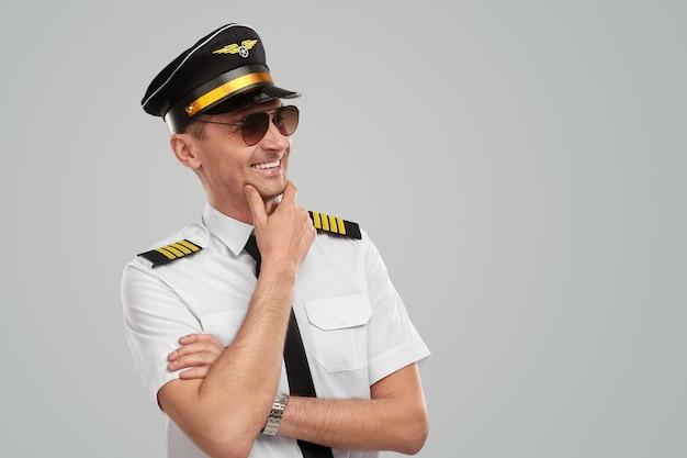 Mężczyzna pilot w dowództwie myśli i uśmiecha się