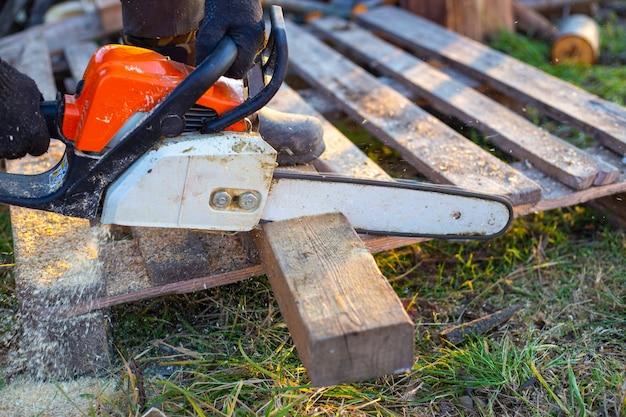 Mężczyzna piłuje deskę piłą łańcuchową. przygotowanie drewna opałowego na zimę.