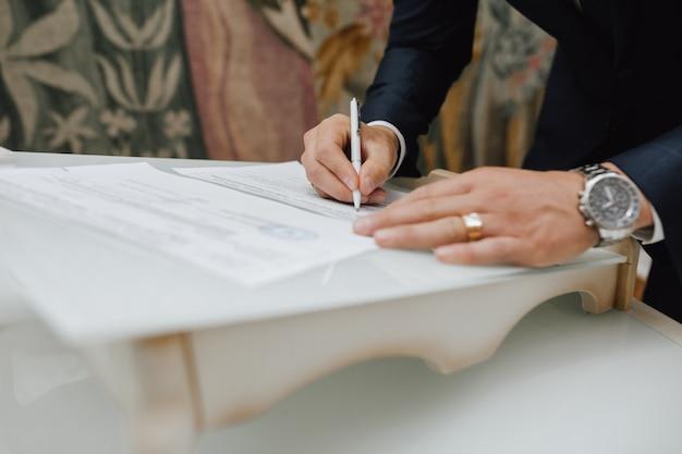 Mężczyzna piórem podpisuje dokument