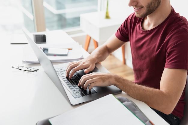 Mężczyzna pisać na maszynie na jego klawiaturowym wysokim widoku