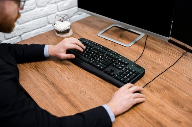 Mężczyzna pisać na maszynie na klawiatury zakończeniu up
