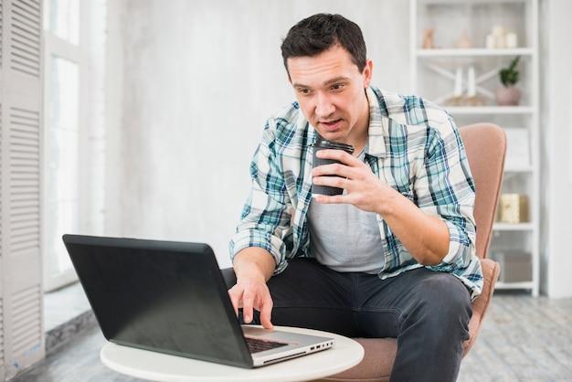 Mężczyzna pisać na maszynie na laptopie i trzyma filiżankę napój na krześle