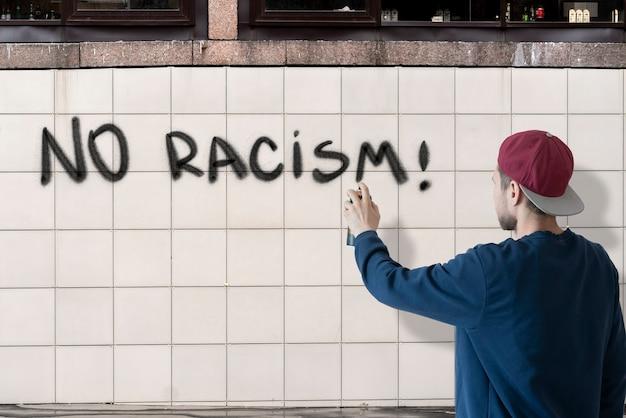 Mężczyzna piszący farbą w sprayu może powstrzymać brak rasizmu na ścianie, koncepcja symbolu graffiti