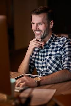 Mężczyzna piszący na klawiaturze komputera w domowym biurze