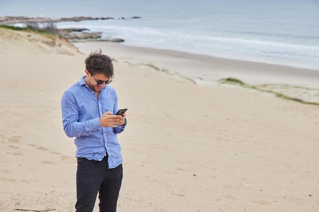 Mężczyzna piszący na swoim smartfonie stojąc na plaży, podczas gdy w tle widać morze, piasek i piękne fale.
