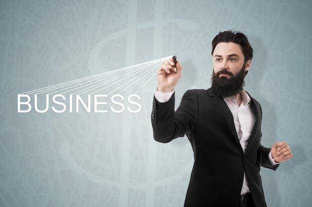Mężczyzna pisze biznes napis na tle symbolu dolarów