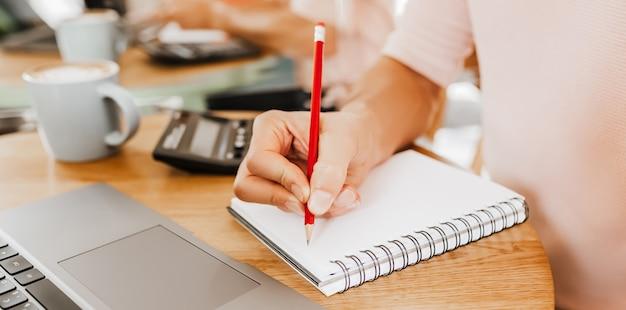 Mężczyzna pisze informacje biznesowe w notesie w miejscu pracy w biurze z kalkulatorem i laptopem