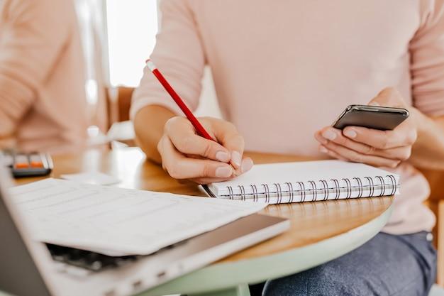 Mężczyzna pisze informacje biznesowe w notesie w miejscu pracy w biurze ze smartfonem