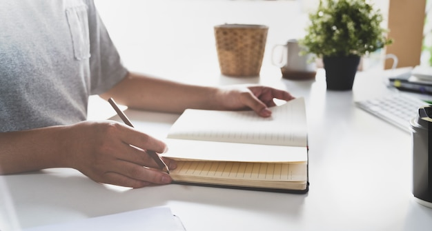 Mężczyzna pisze jego pomysłów pojęciach na notatniku
