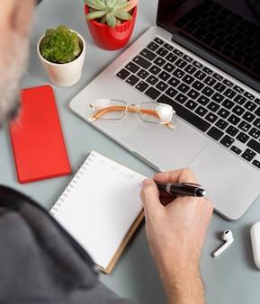 Mężczyzna pisze listę rzeczy do zrobienia w pobliżu laptopa na szarym biurku z bliska