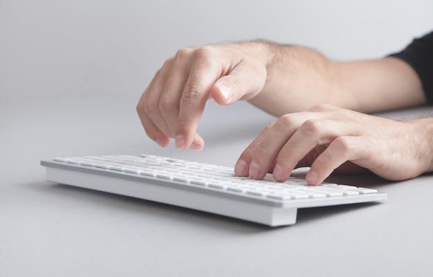 Mężczyzna pisze na klawiaturze komputera.